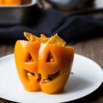 Halloween Jack O'Lantern stuffed peppers, straight angle. White plate.