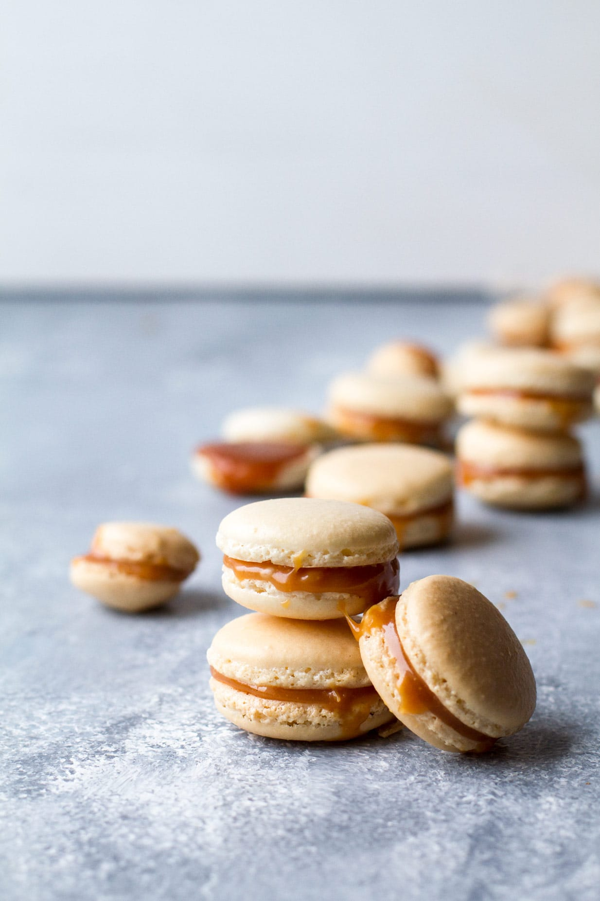 Salted Caramel Macarons with Homemade Caramel Filling stacked on top of each other, many blurry macarons in the background.