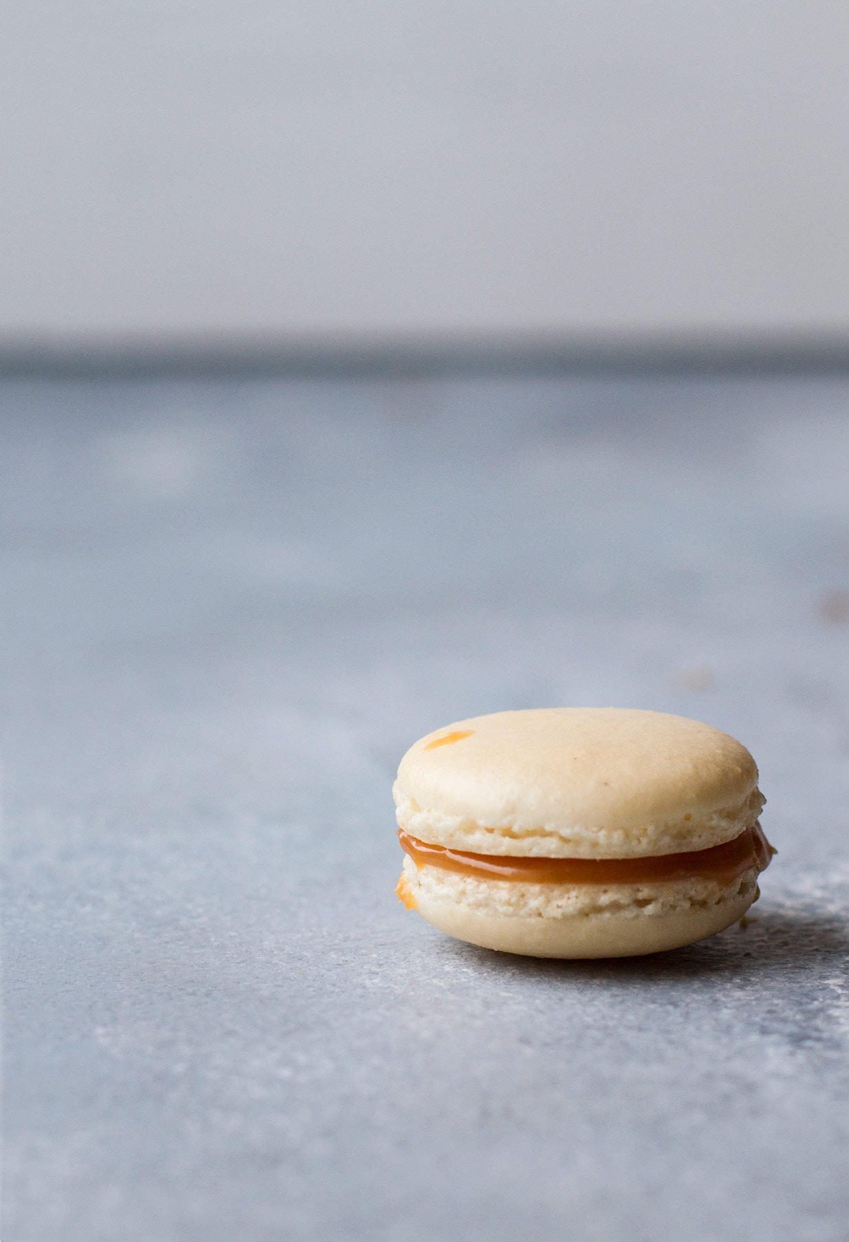 a single Salted Caramel Macaron with Homemade Caramel in the right corner, blue blurry background.