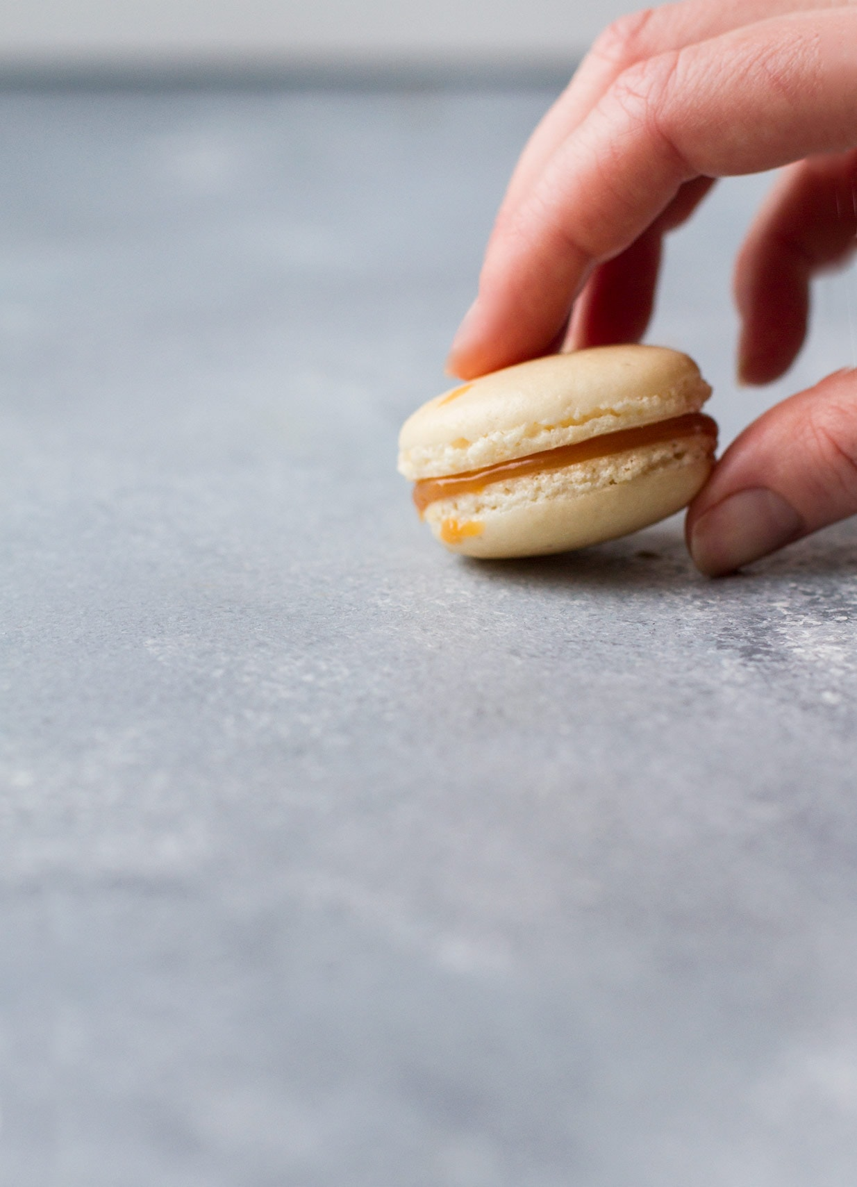 Hand reaching for one salted caramel macaron.