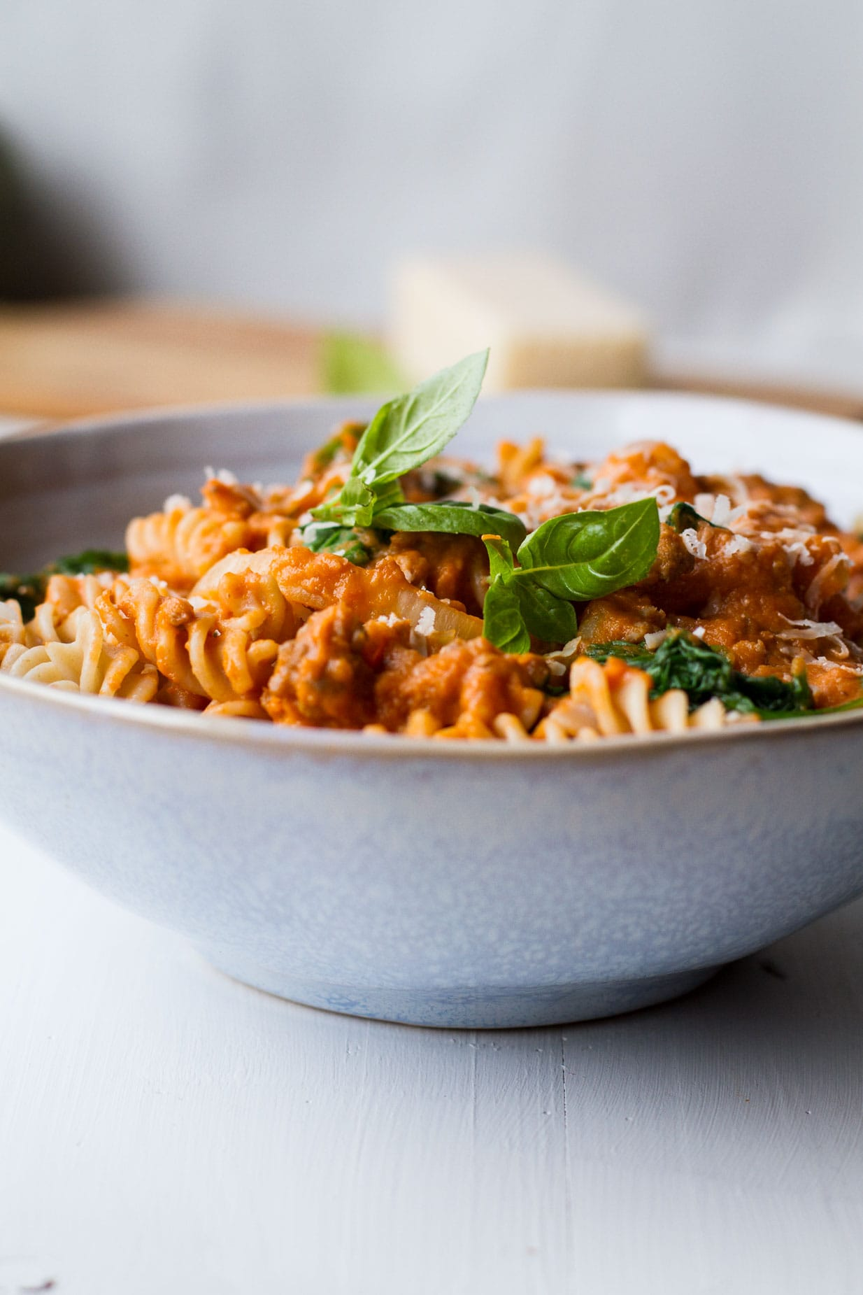 Creamy Parmesan Pumpkin Pasta in a blue bowl, garnished with fresh basil.