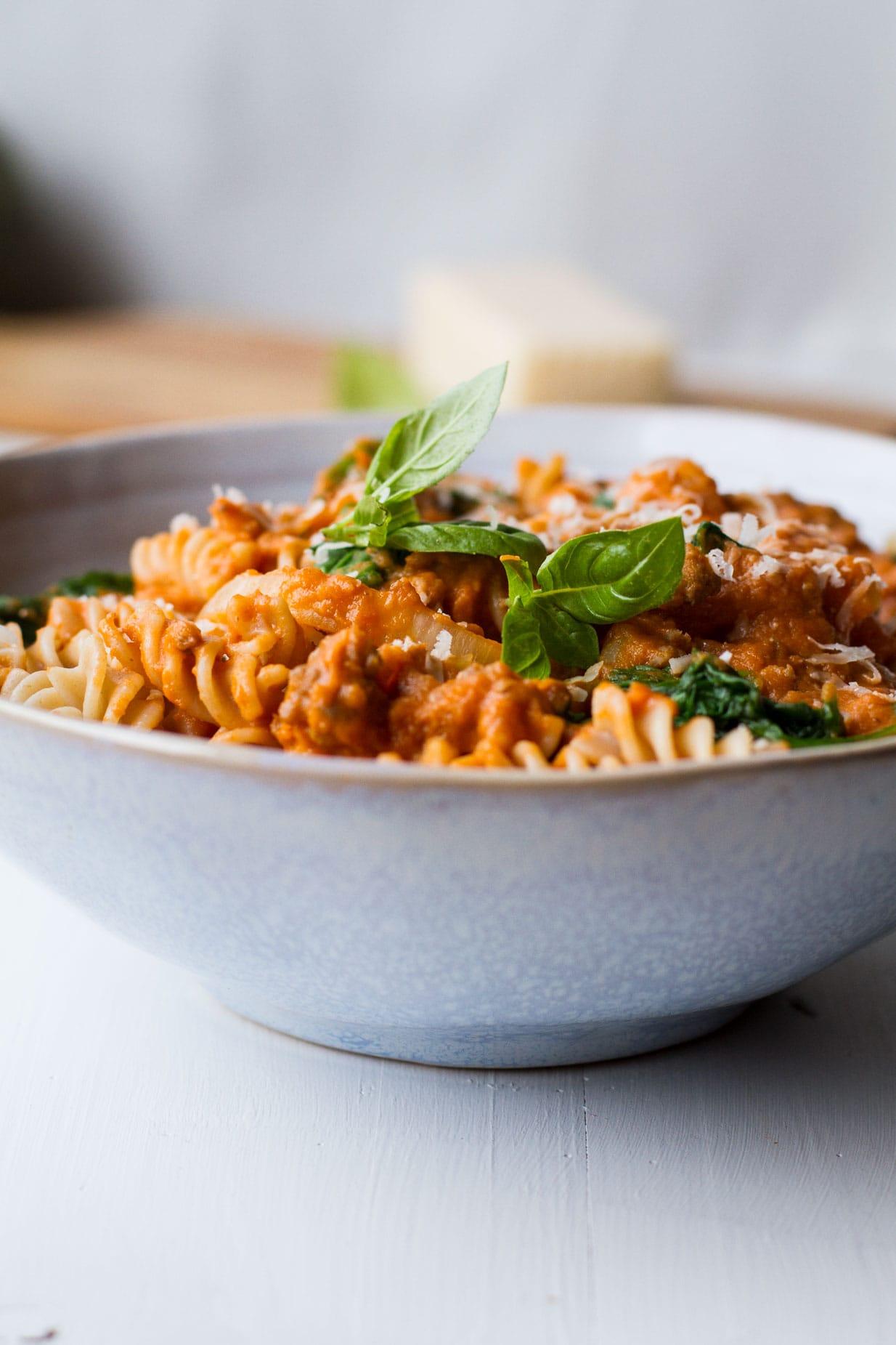 Creamy Parmesan Pumpkin Pasta in a blue bowl, garnished with fresh basil.