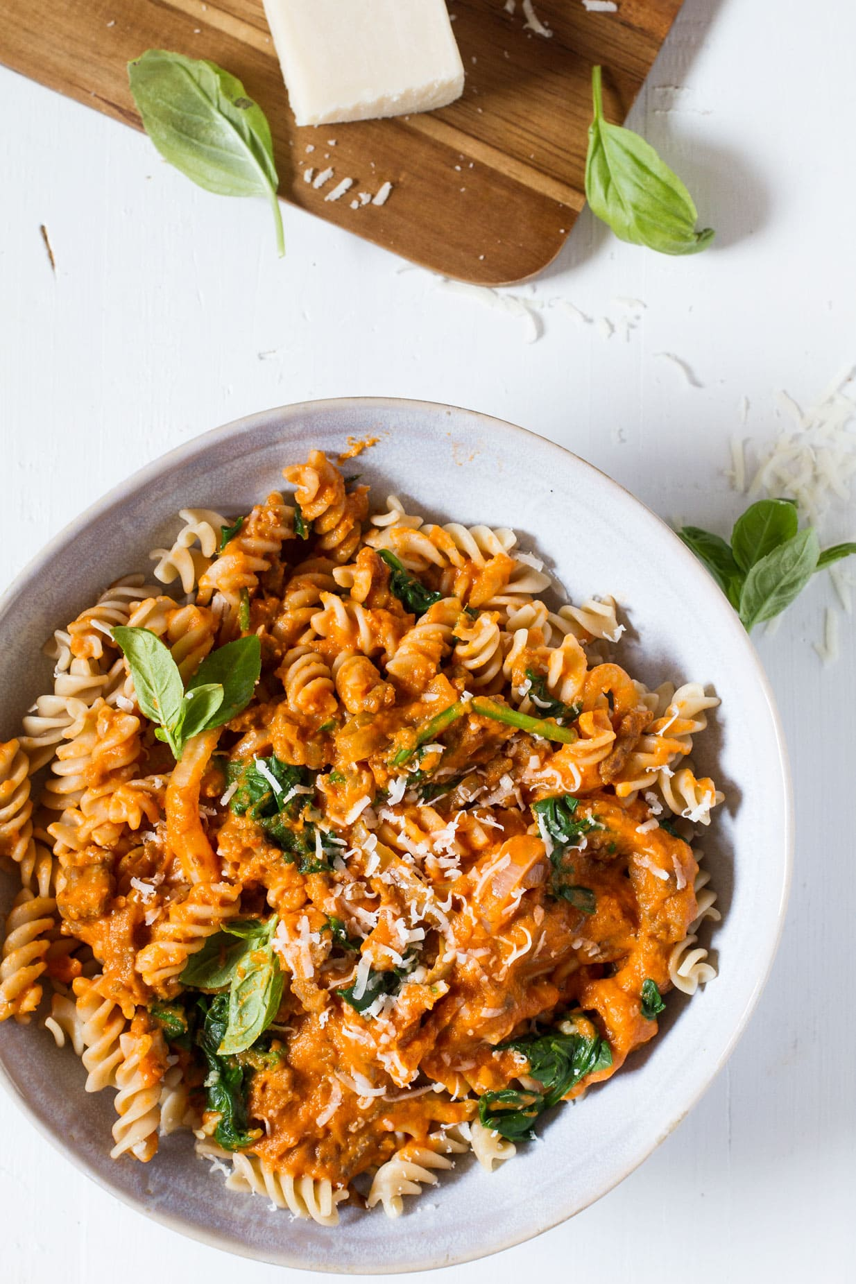 Creamy Parmesan Pumpkin Pasta in a blue bowl, white background and fresh parmesan in the left top corner.
