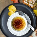 Pumpkin creme brulee on a small white plate on a bigger black plate. Leaves scattered around.