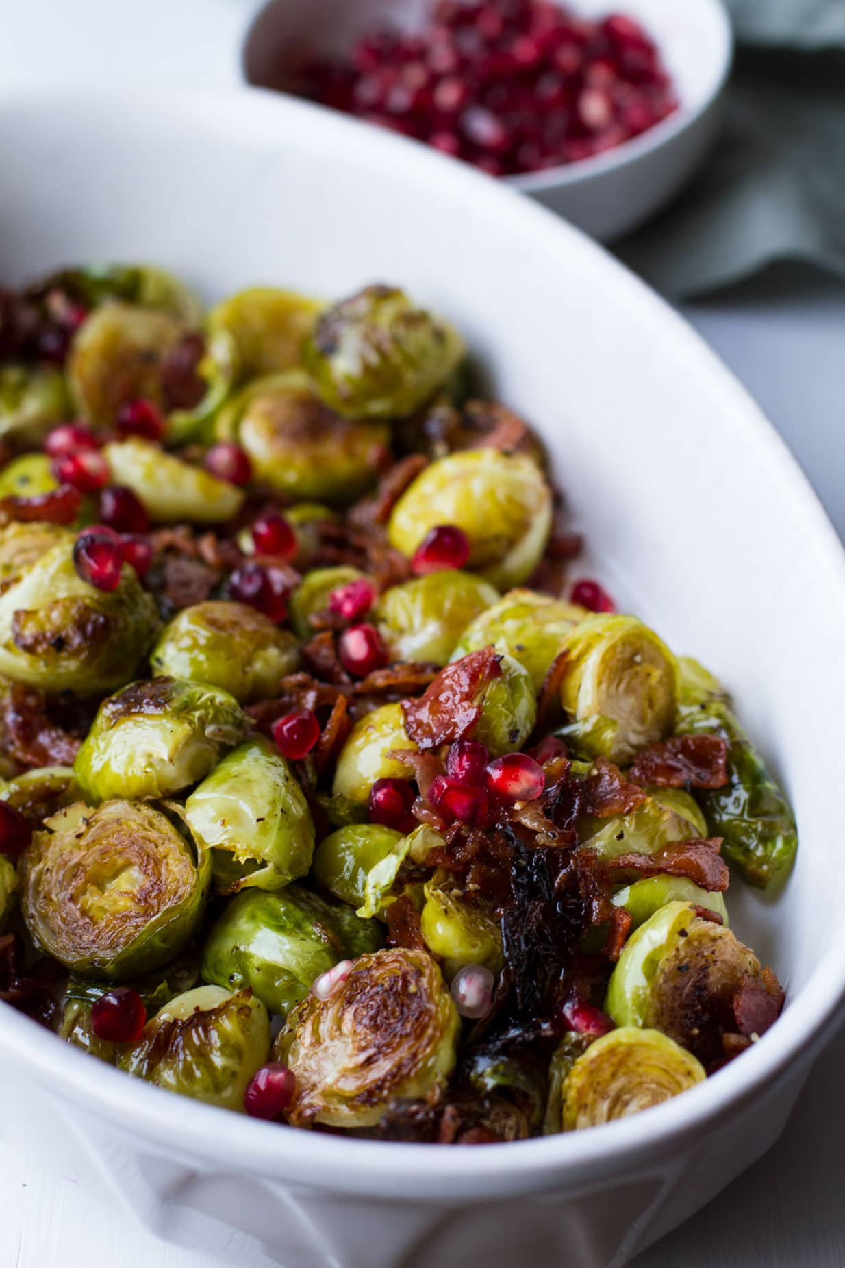 Perfect freezer meals: honey balsamic baked brussels sprouts in a white dish with pomegranate.