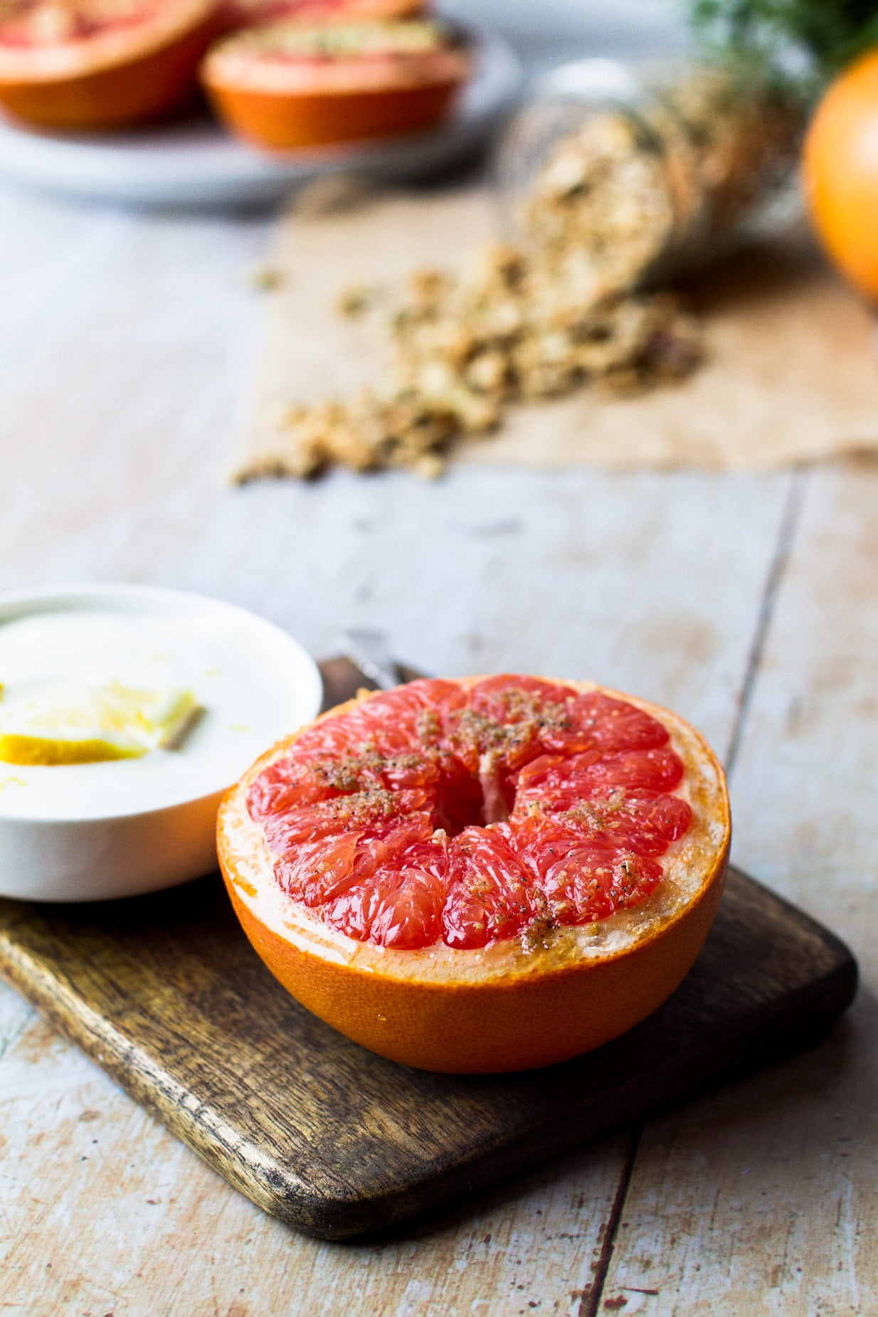 Halved baked grapefruit on a dark wooden tray, white bowl of yoghurt with lemon and a tipped over jar of granola in the background