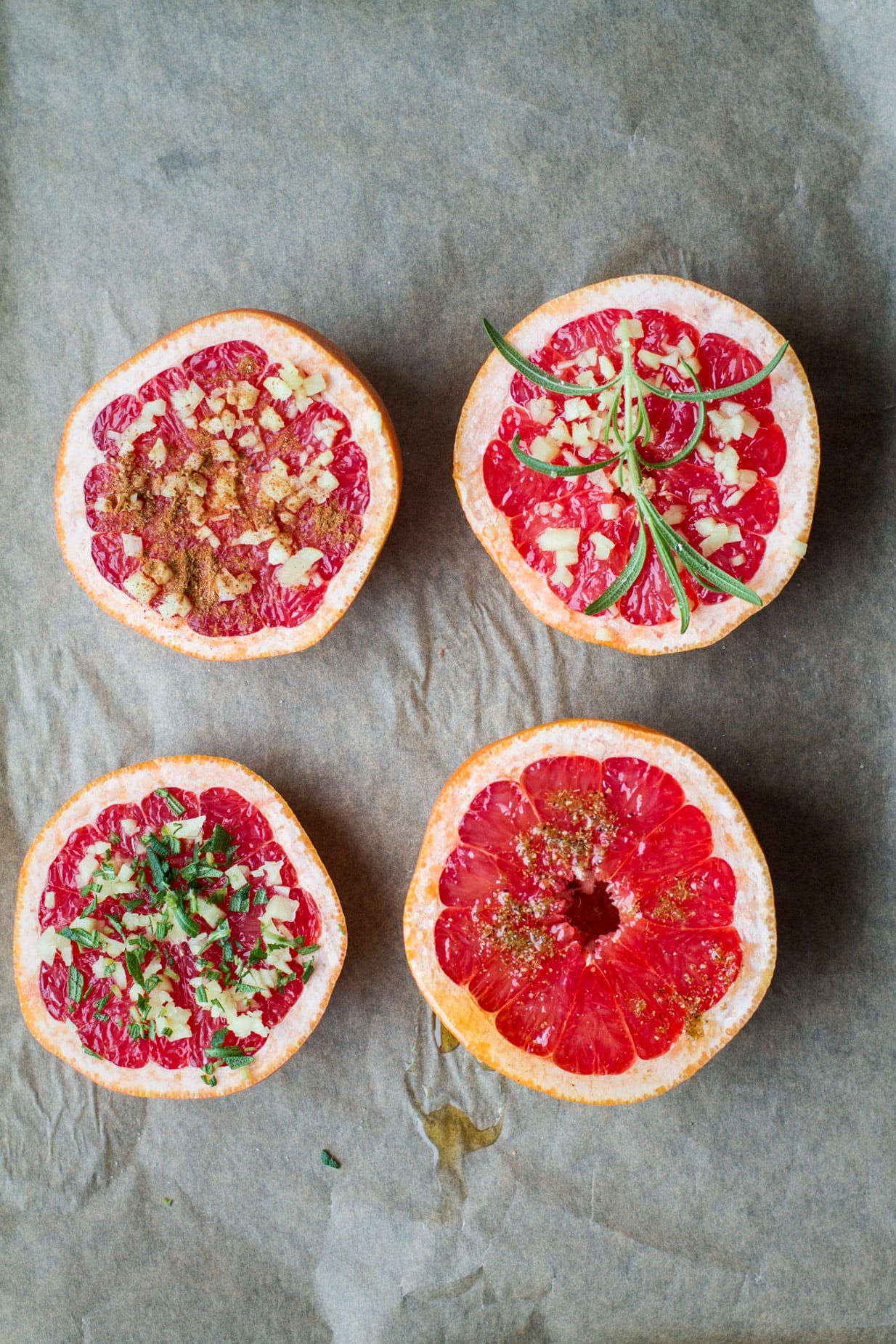 4 unbaked half grapefruits, two with rosemary, one with spice blends and one with a wet honey look