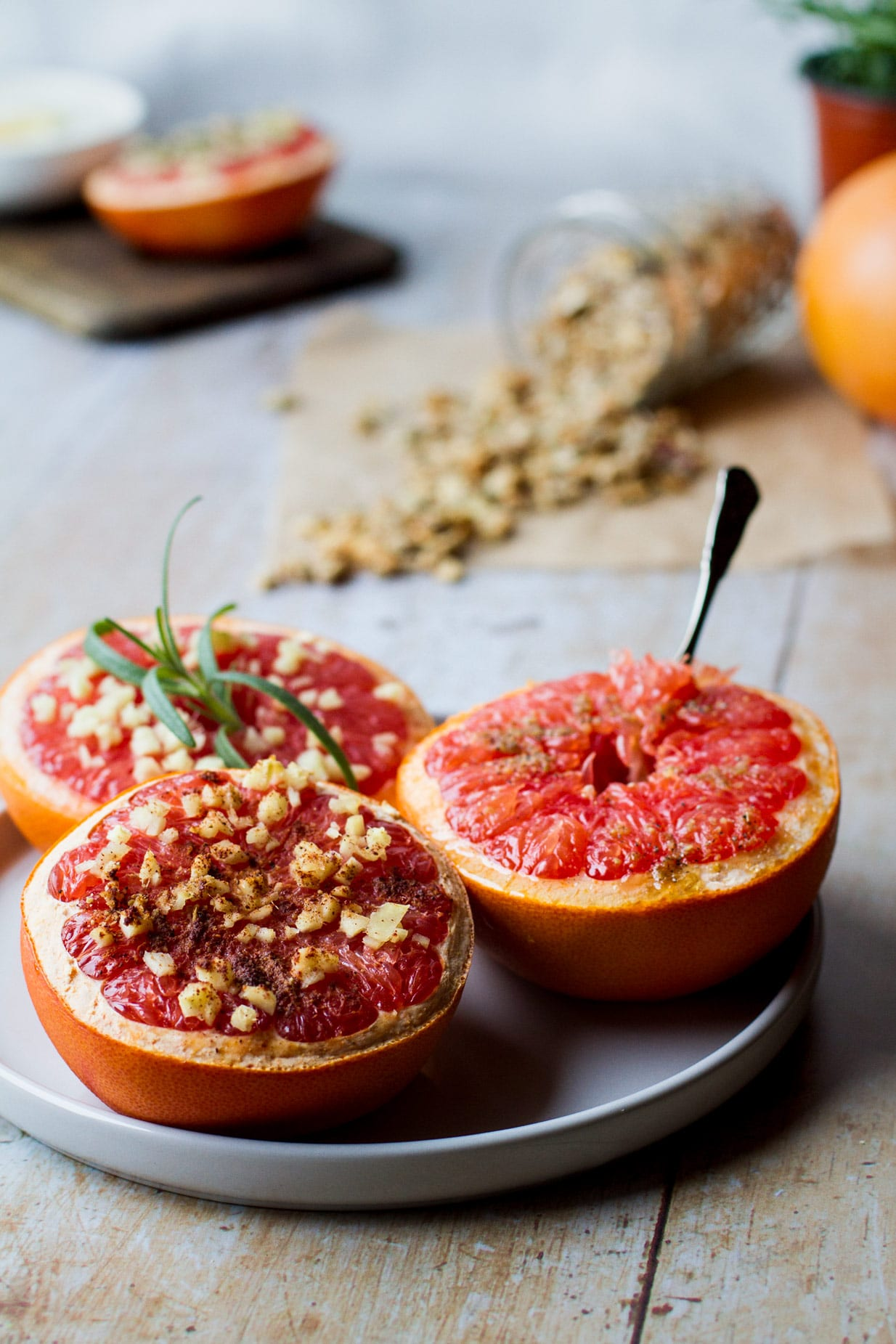 3 halved baked grapefruits on a white plate, one with a spoon in, one with a rosemary sprig on and one with spice sprinkle and ginger on top and a tipped over jar of granola in the background