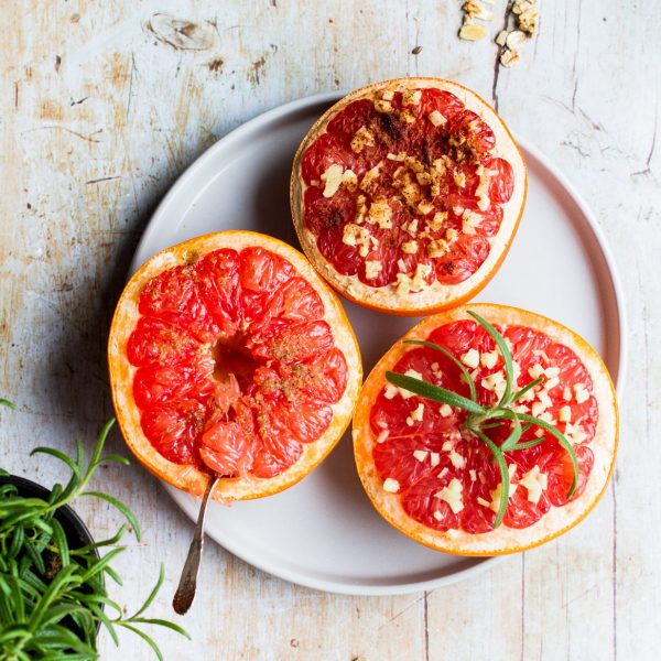 Bird's eye view of three half grapefruits on a beige plate and a light wooden background. One has a spoon in, one has rosemary on and one has spice sprinkles. A little rosemary and granola in the corner of the shot.