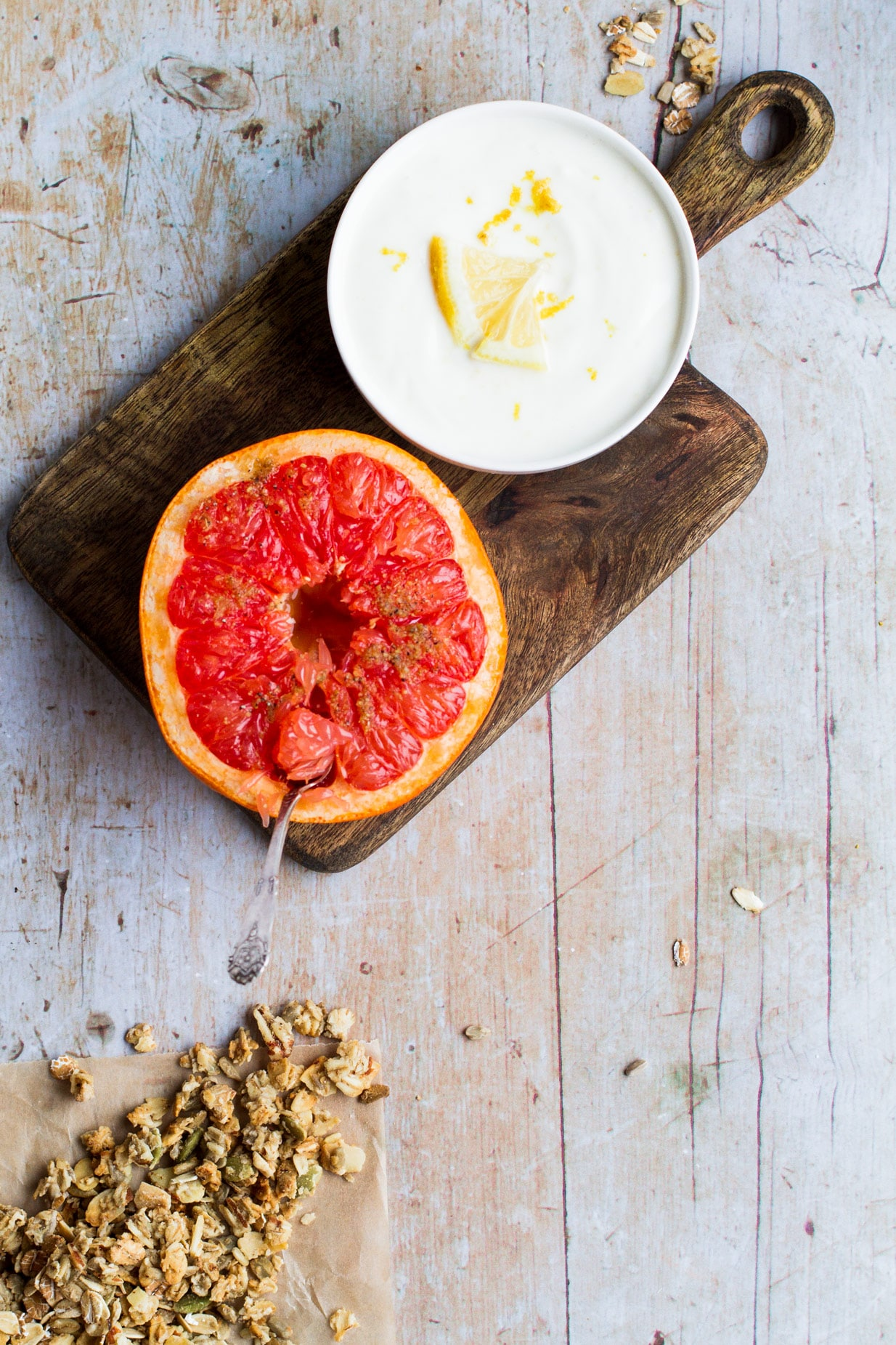 Bird's eye view of a halved baked grapefruit on a dark wooden tray with a white bowl of yoghurt with lemon garnish. A sprinkle of granola on the light wooden table.