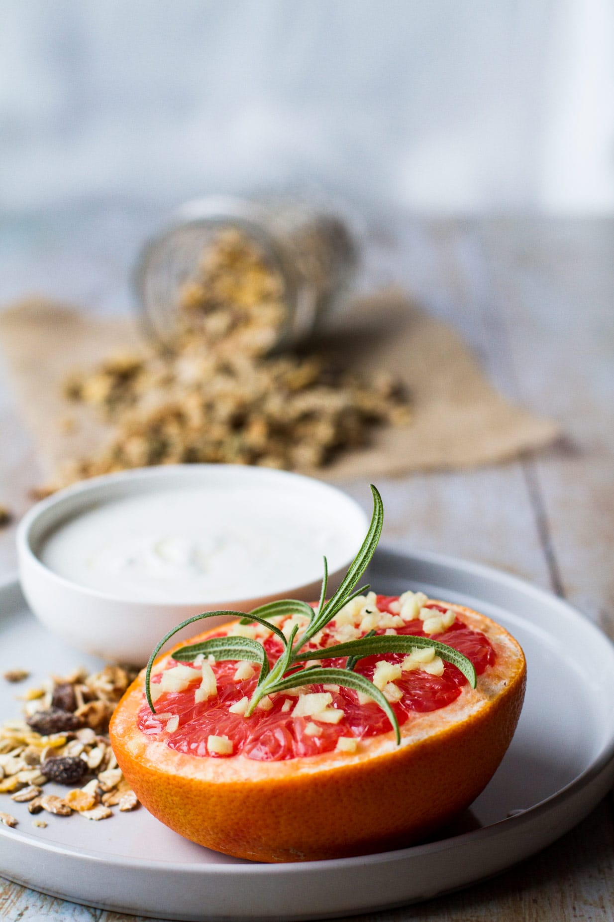 Baked grapefruit on a white plate, with granola a white bowl of yoghurt and a tipped over glass jar of granola in the back