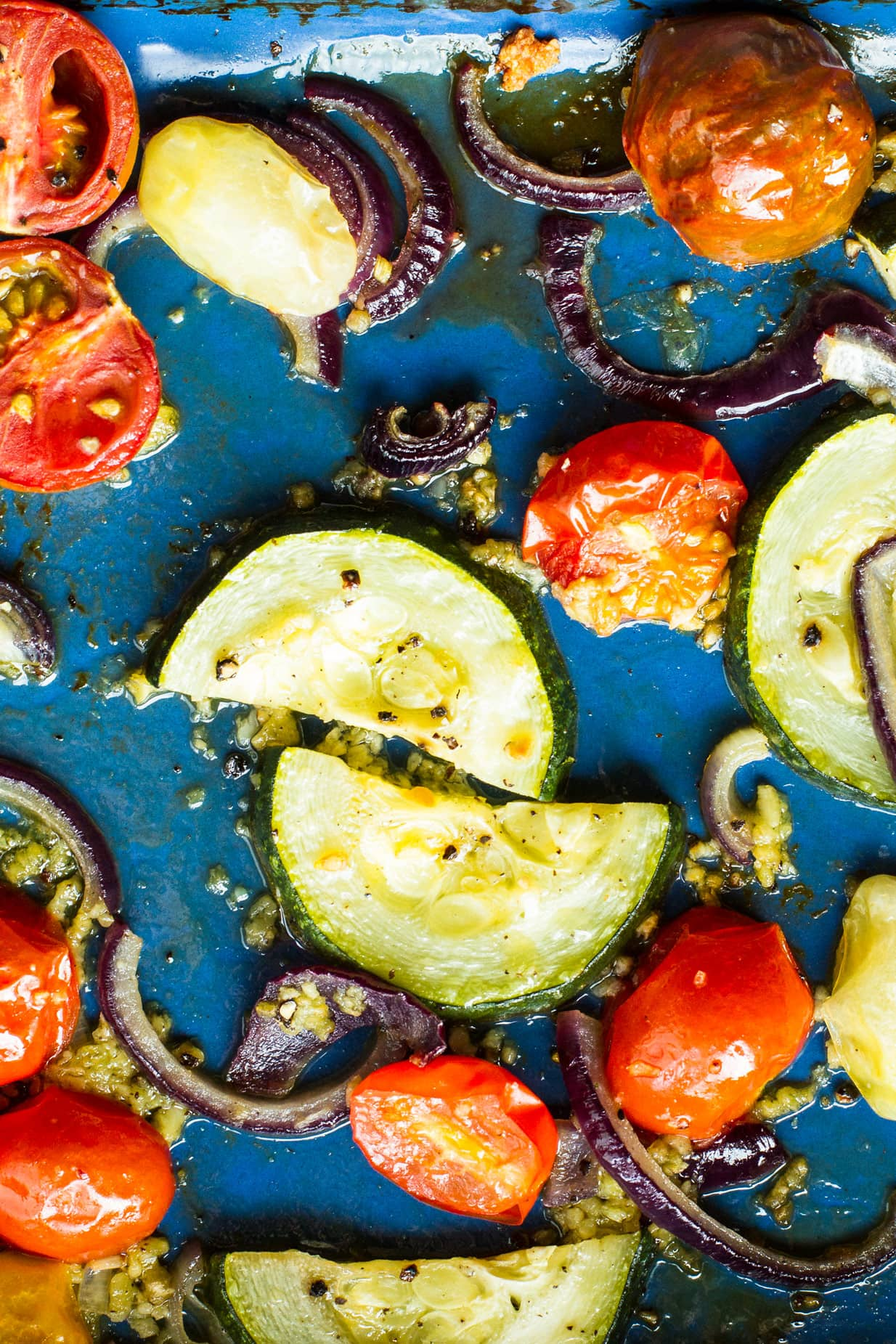 Garlic roasted tomatoes, zucchini slices and red onion in a blue pan.