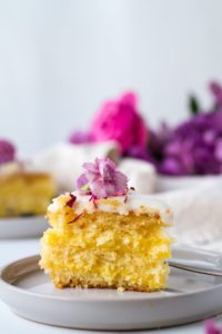 Yellow slice of cake on a grey plate with a purple flower on top. More purple flowers in the background.