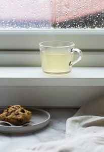 Clear mug with pale yellow drink in the window frame. Cookies on the table.