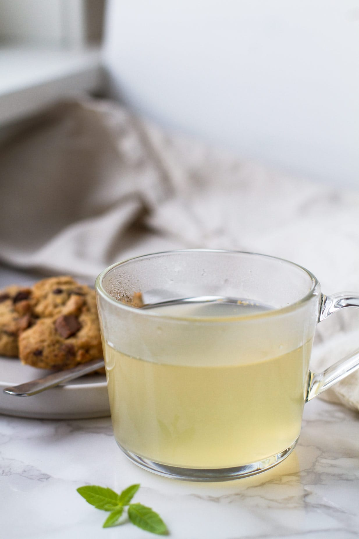 Clear mug with a pale yellow drink. Cookies in the background.