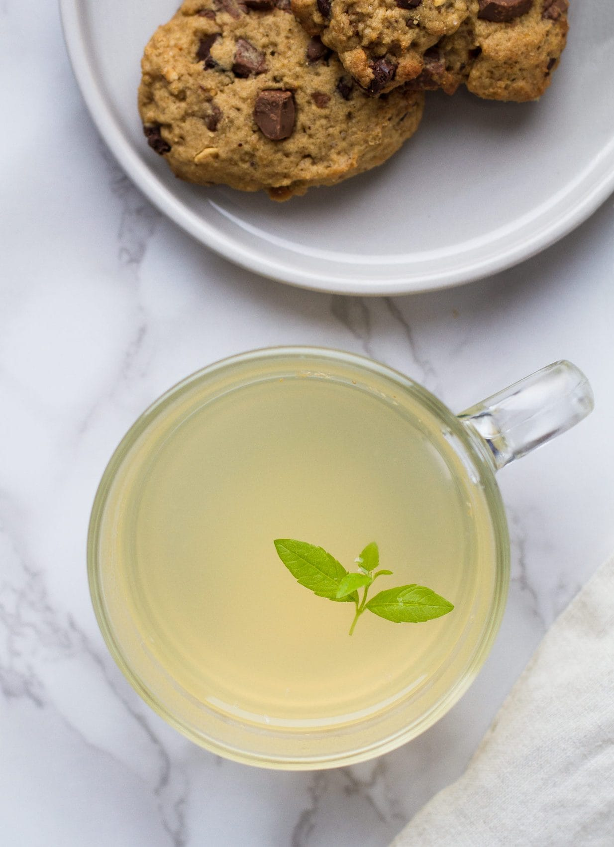 Bird's eye view of the pale yellow drink. Cookies in the upper right corner