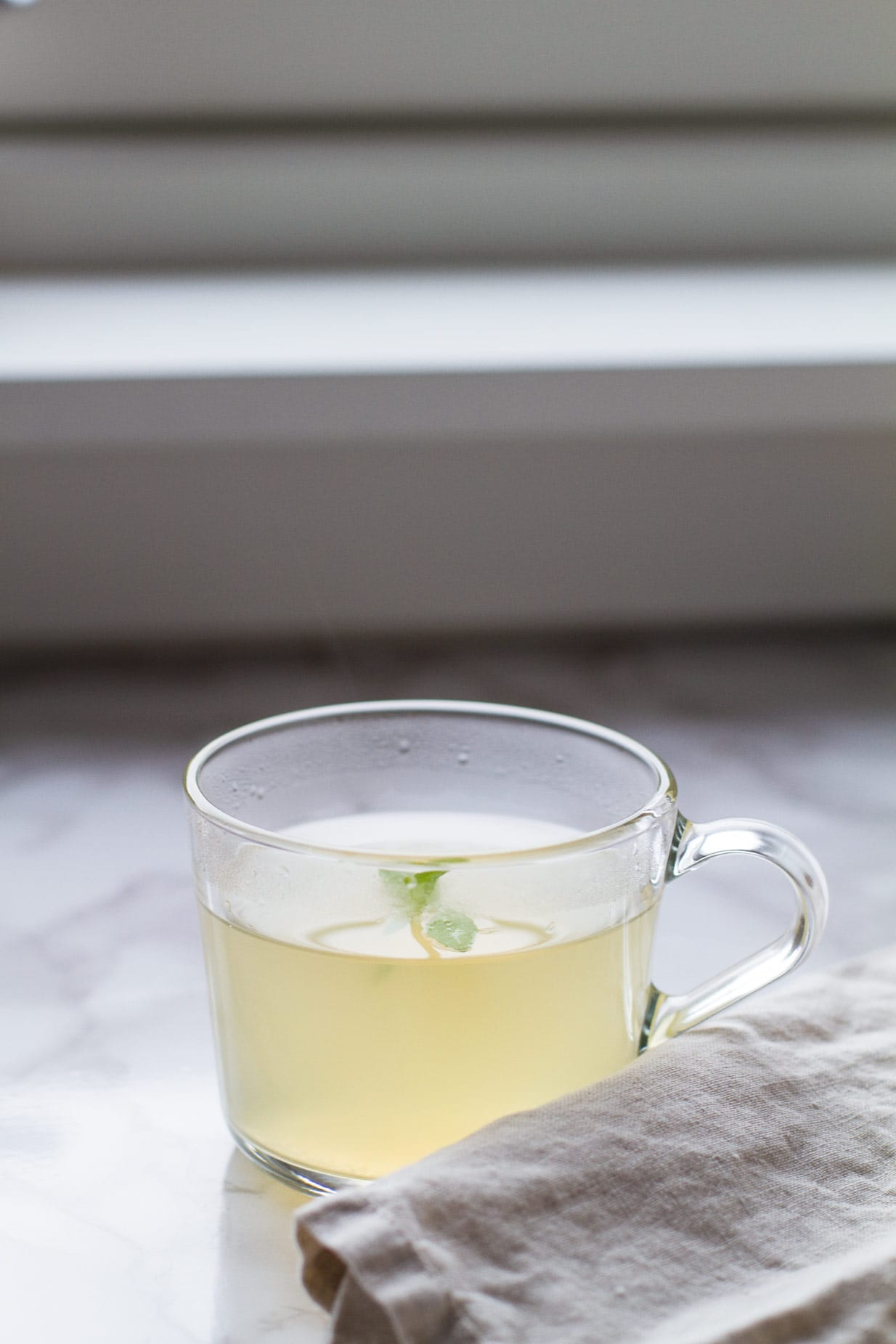 Clear mug with pale yellow drink and lemon verbena garnish.