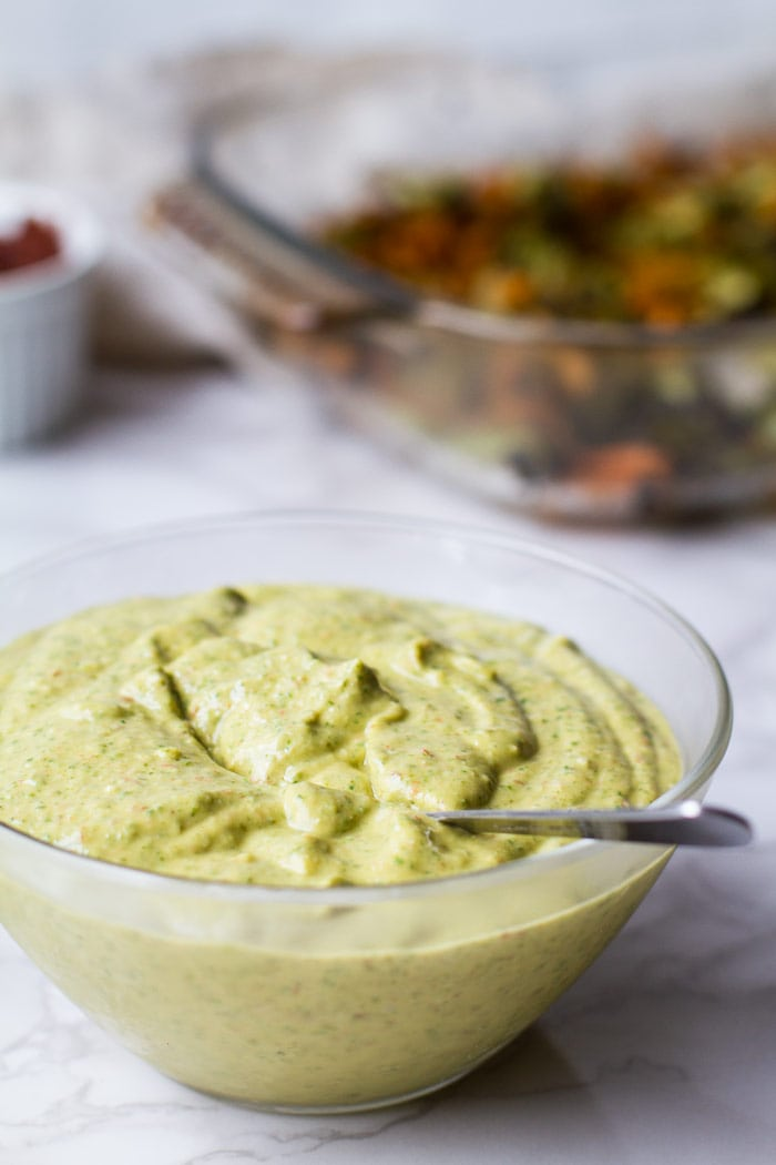 A clear bowl with avocado sauce and a spoon. Roasted vegetables blurred out in the background.