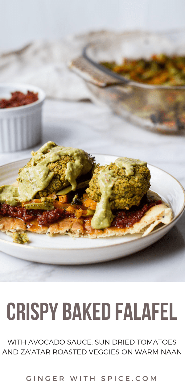 A naan with sun-dried tomatoes paste, roasted vegetables baked falafel patties and avocado sauce on a white plate and white marble background. Pinterest pin