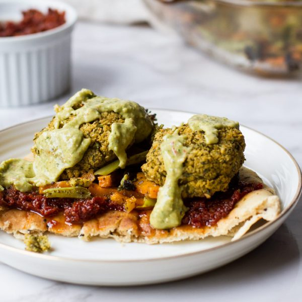 A naan with sun-dried tomatoes paste, roasted vegetables baked falafel patties and avocado sauce on a white plate and white marble background.