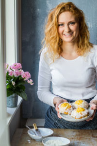 Girl with red hair and white shirt holding a beige plate with three vanilla custard and coconut sweet buns. Pink flower in the back.