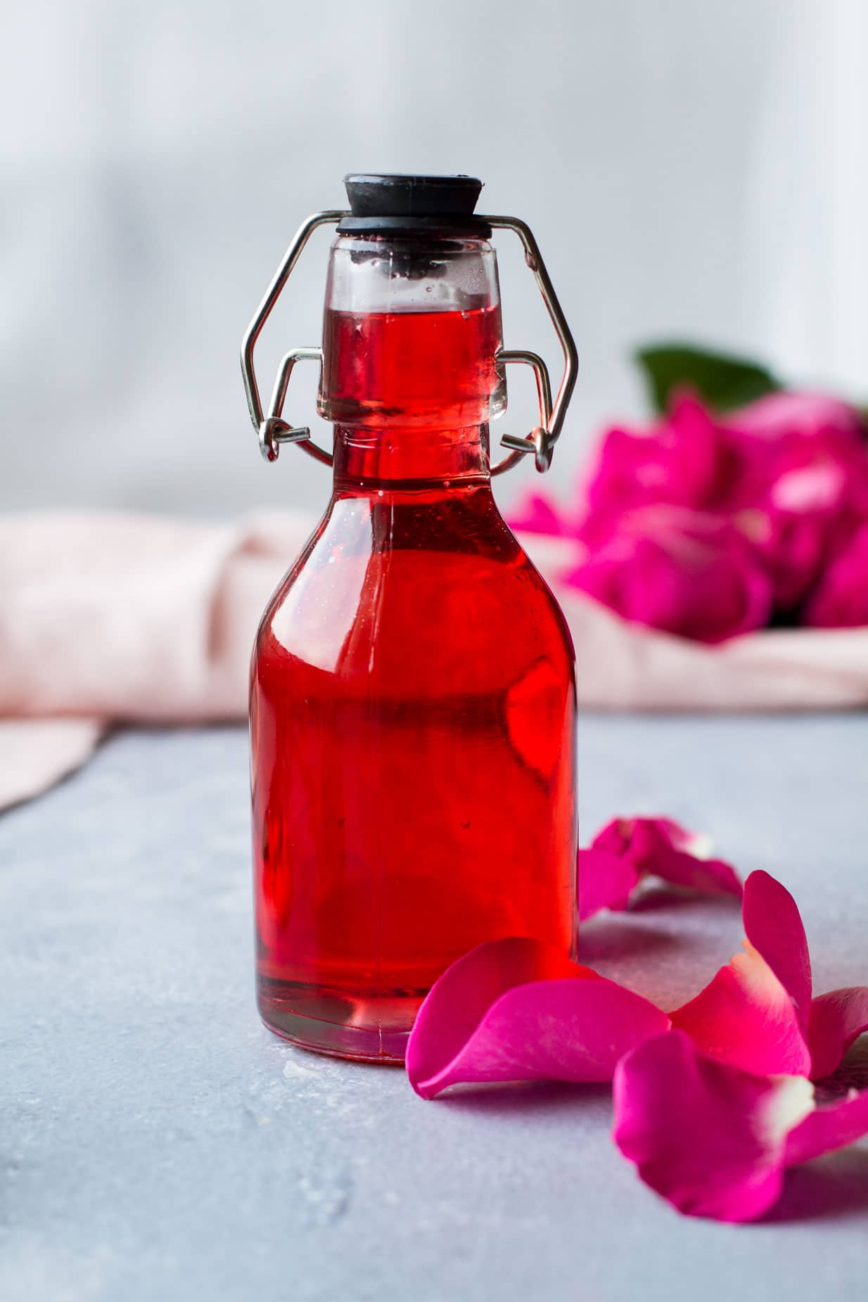 Red rose syrup in a clear bottle. Pink flowers in the background.