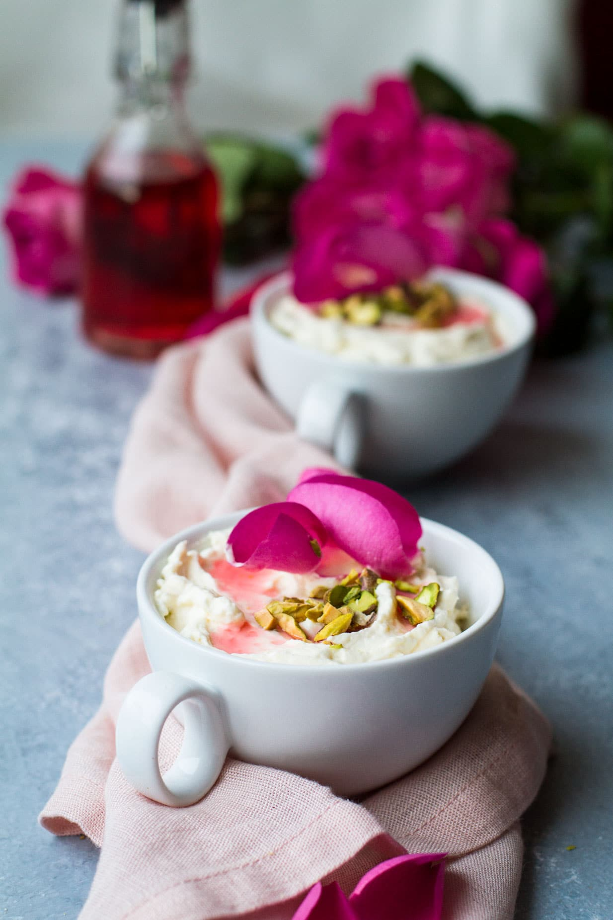 White cup with white mouse, chopped pistachios and rose petals. Roses and another cup blurred in the background. Blue table and pink cloth.