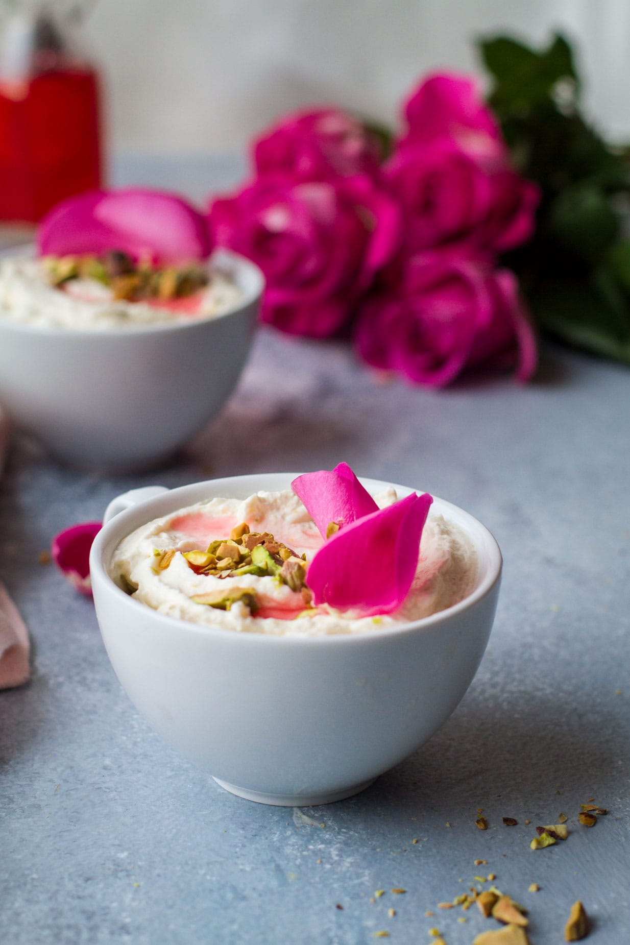 White cup with white chocolate mouse, chopped pistachios and rose petals. Roses and another cup blurred in the background. Blue table.