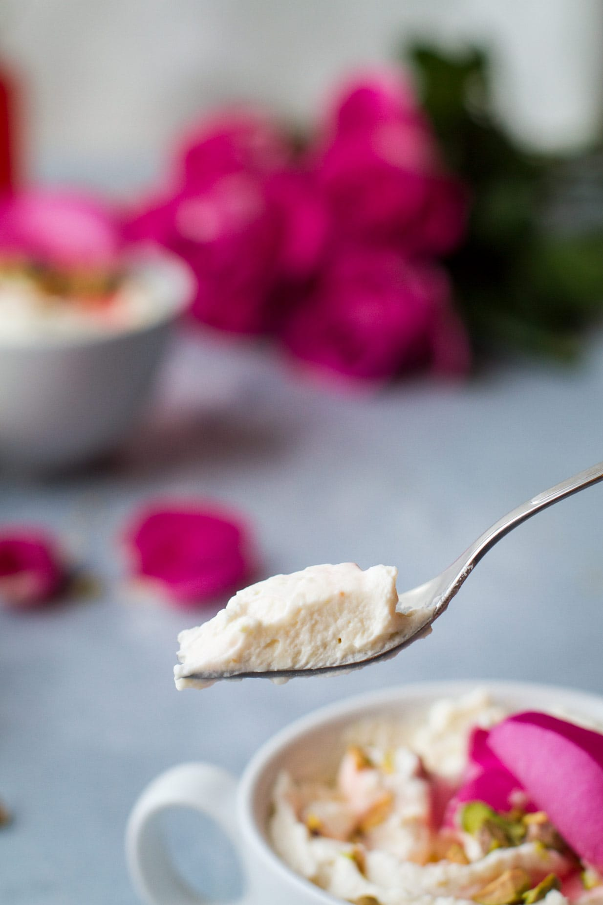 Closeup of a fork with a bite of white chocolate mousse. Cup with white chocolate mousse and roses are blurred in the background.