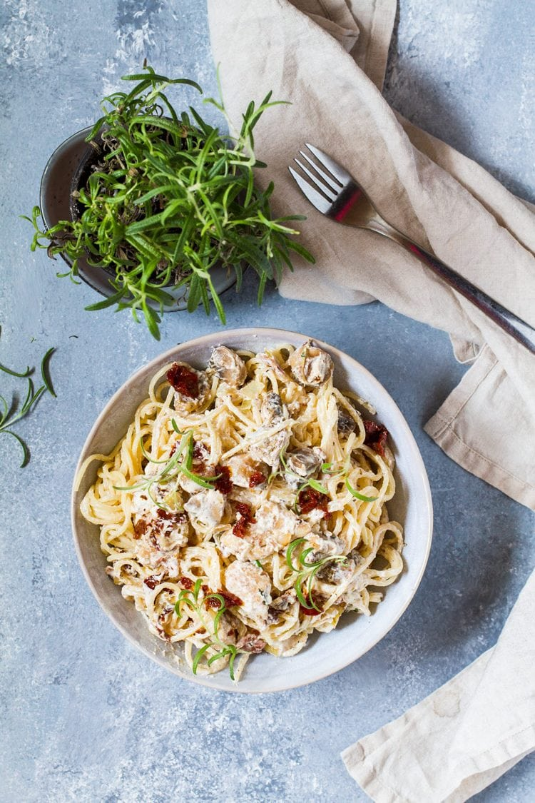 Bird's eye view of a blue bowl with creamy sun dried tomato pasta. A rosemary plant and nude cloth on blue background.