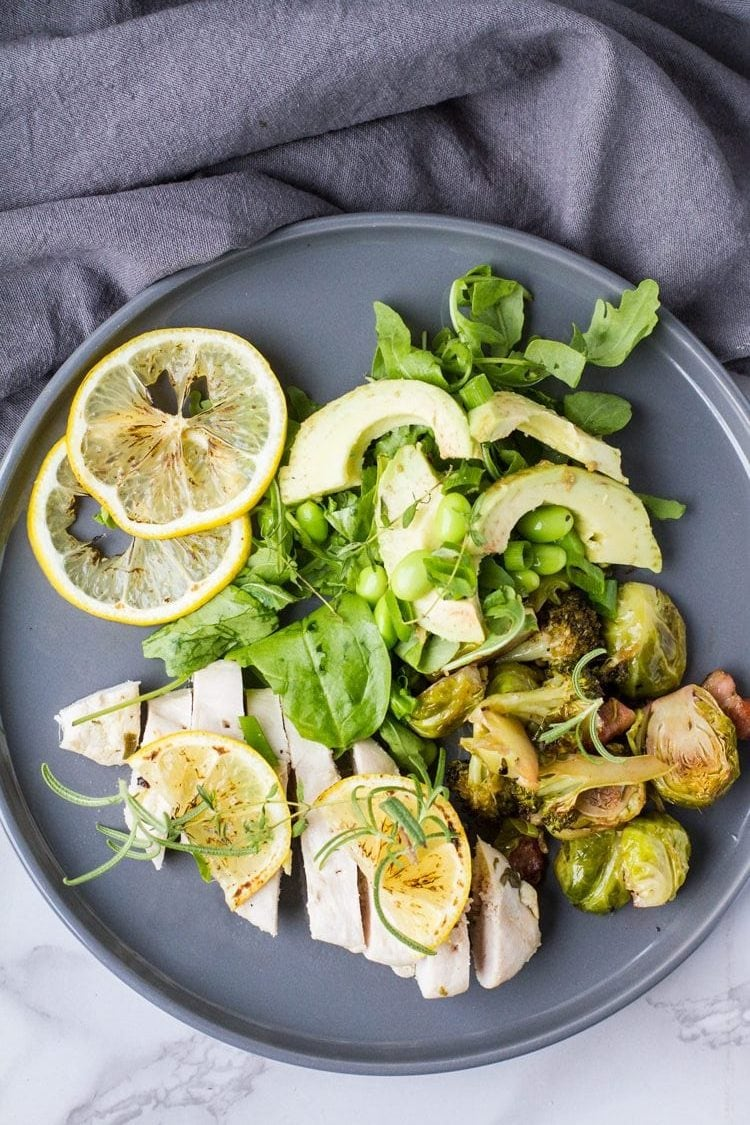 Flat lay of baked lemon chicken with green spring salad and lemon slices, dark grey plate. Turned to be horizontal.