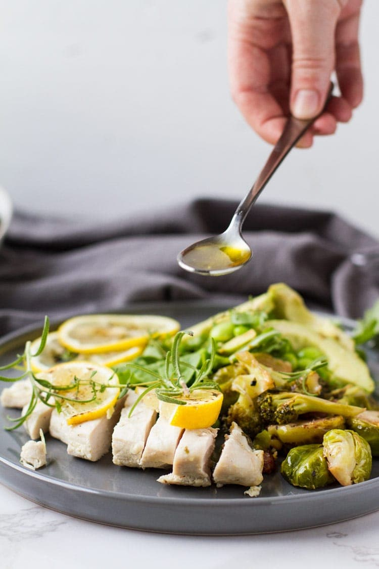 Drizzling lemon garlic sauce over baked lemon chicken and green spring salad. Grey cloth.