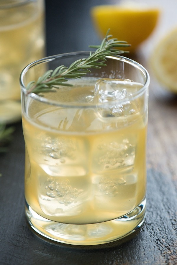 Lemon Rosemary Bourbon Sour in a clear glass with ice cubes and rosemary garnish.