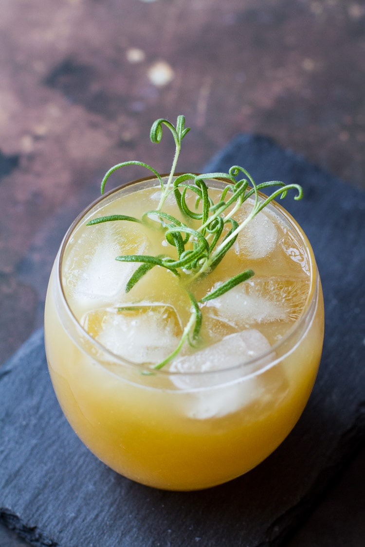 Penicillin cocktail with ice cubes and rosemary sprig in a round class. On top of a stone plate.