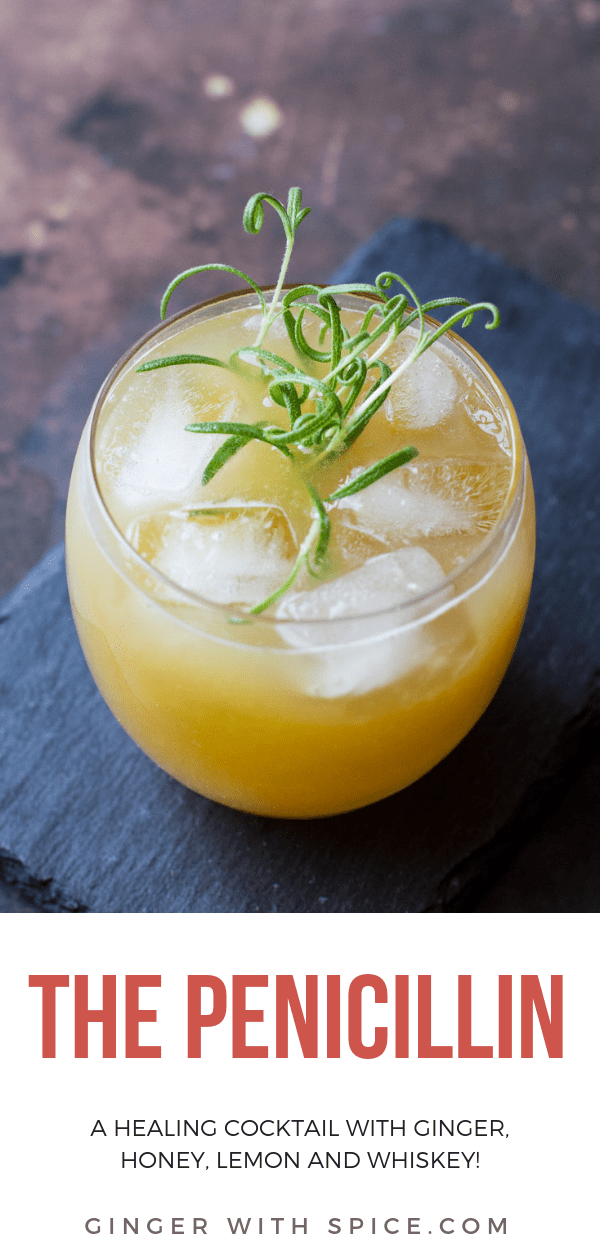 Penicillin cocktail with ice cubes and rosemary sprig in a round class. On top of a stone plate. Pinterest pin.