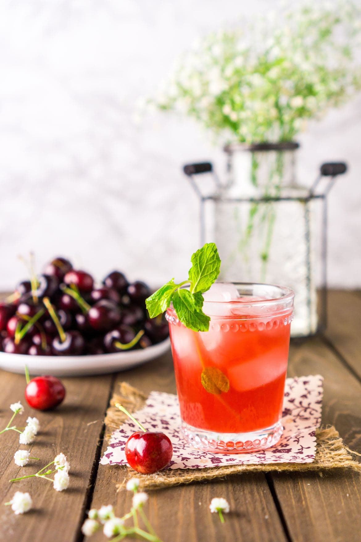 Cherry Bourbon Cocktail on a patterned napkin with a plate of cherries in the background.