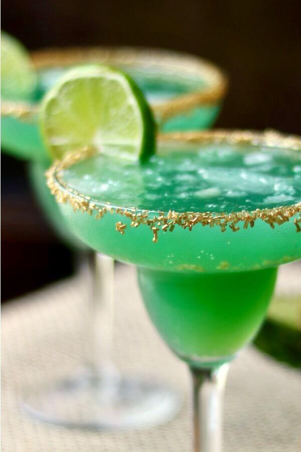 Green Irish margarita in a margarita glass with sugar rim and lime garnish.