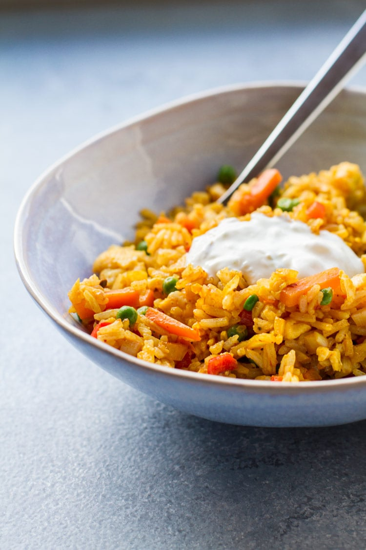 Close-up of yellow fried rice, carrots and peas in a blue bowl.