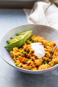 A wide bowl with Mexican fried rice, avocado slices and sour cream. Beige tablecloth in the background.