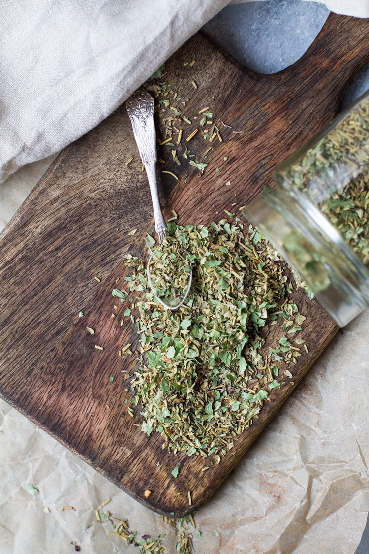 Jar tipped over with Italian seasoning flowing onto a wooden cutting board.