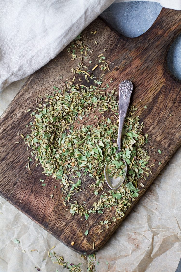 Italian seasoning on a wooden board with a vintage spoon.