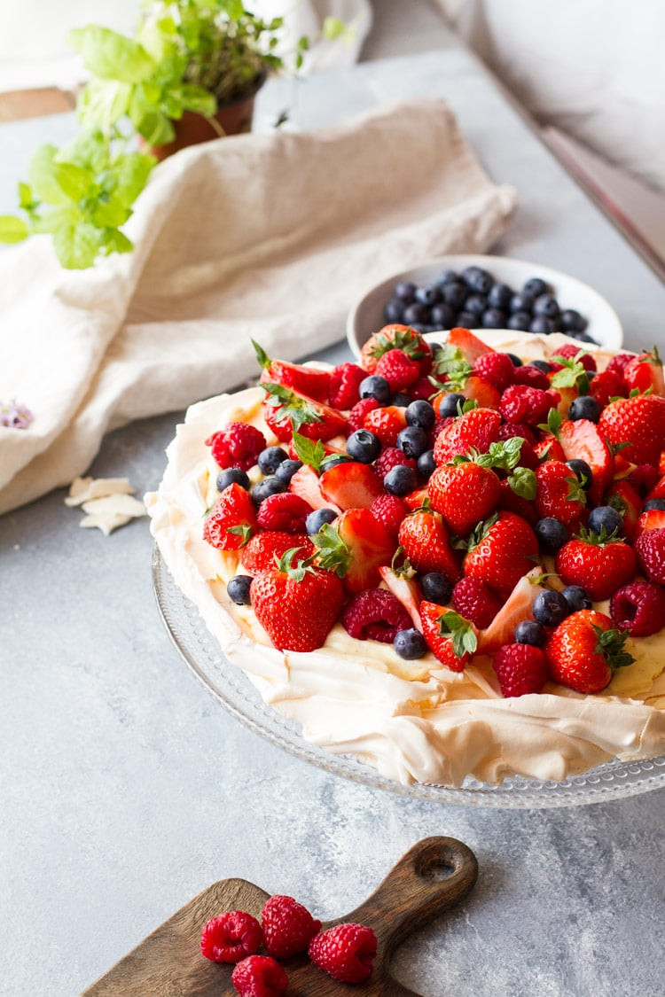 Top of the pavlova filled with strawberries, raspberries and blueberries for pavlova recipe.