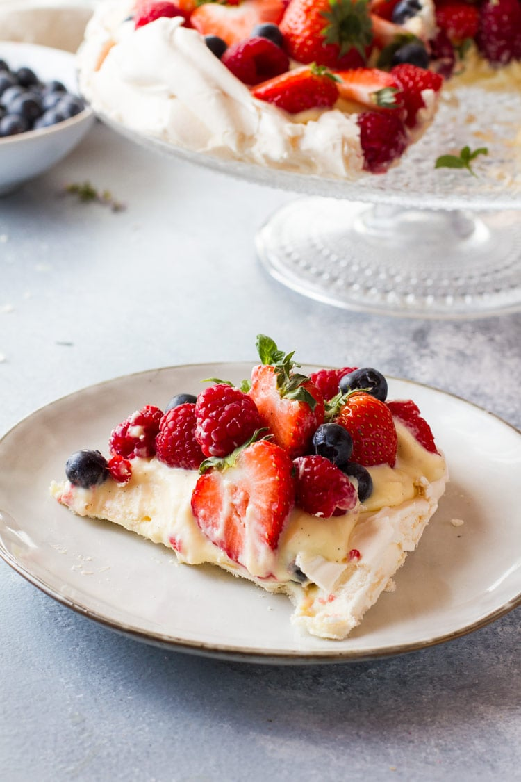 A slice of pavlova cake with fresh berries and pastry cream.