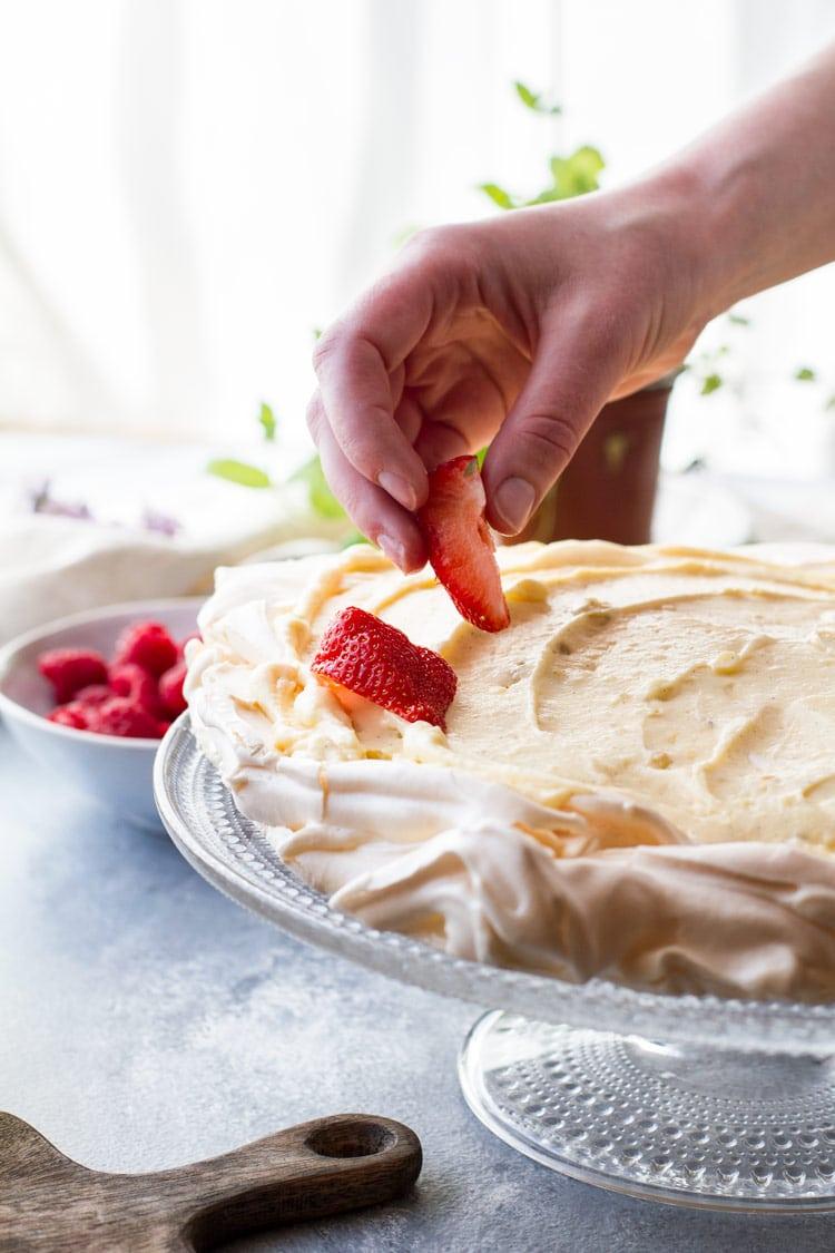 Placing sliced strawberries on pavlova cake with vanilla pastry cream