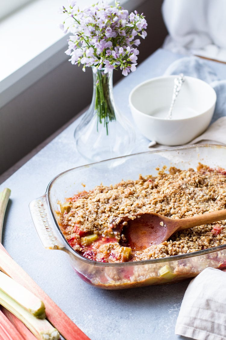 Large baking dish with raspberry rhubarb crisp. Vase with purple flowers and a white bowl.