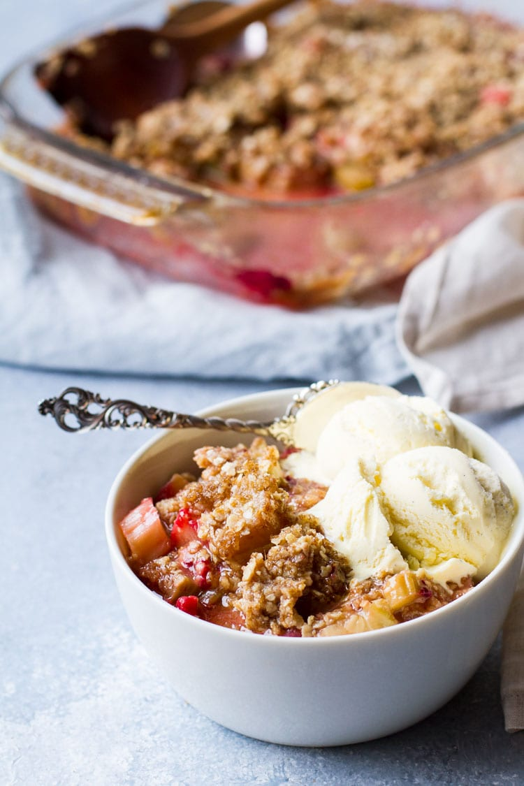 White bowl with rhubarb crisp and two scoops of vanilla ice cream. The complete dish in the background.