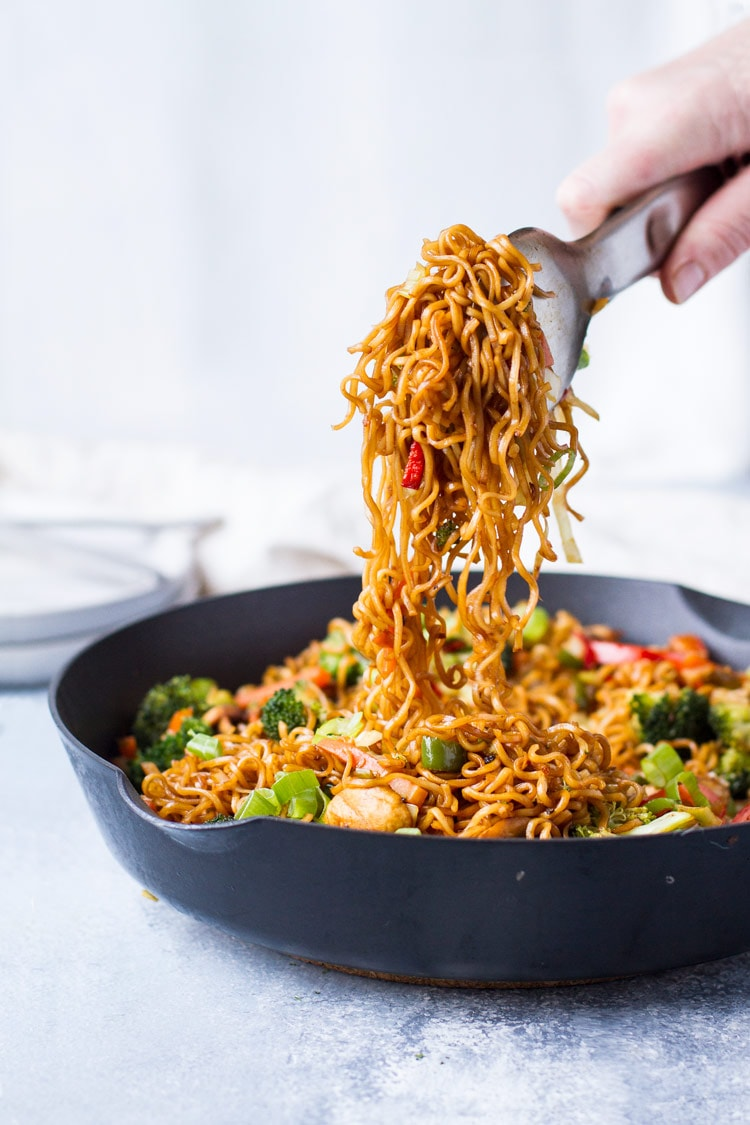 A metal tong holding up noodles from vegetarian lo mein in skillet.