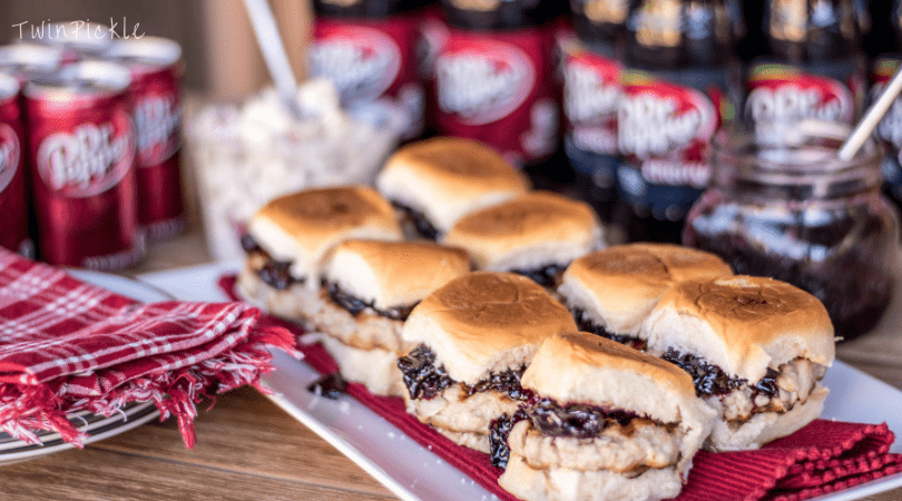 Eight burger sliders and Dr. Pepper cans blurred in the background.
