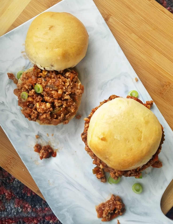 Sloppy joes, one with the bun top and one without. Flatlay.