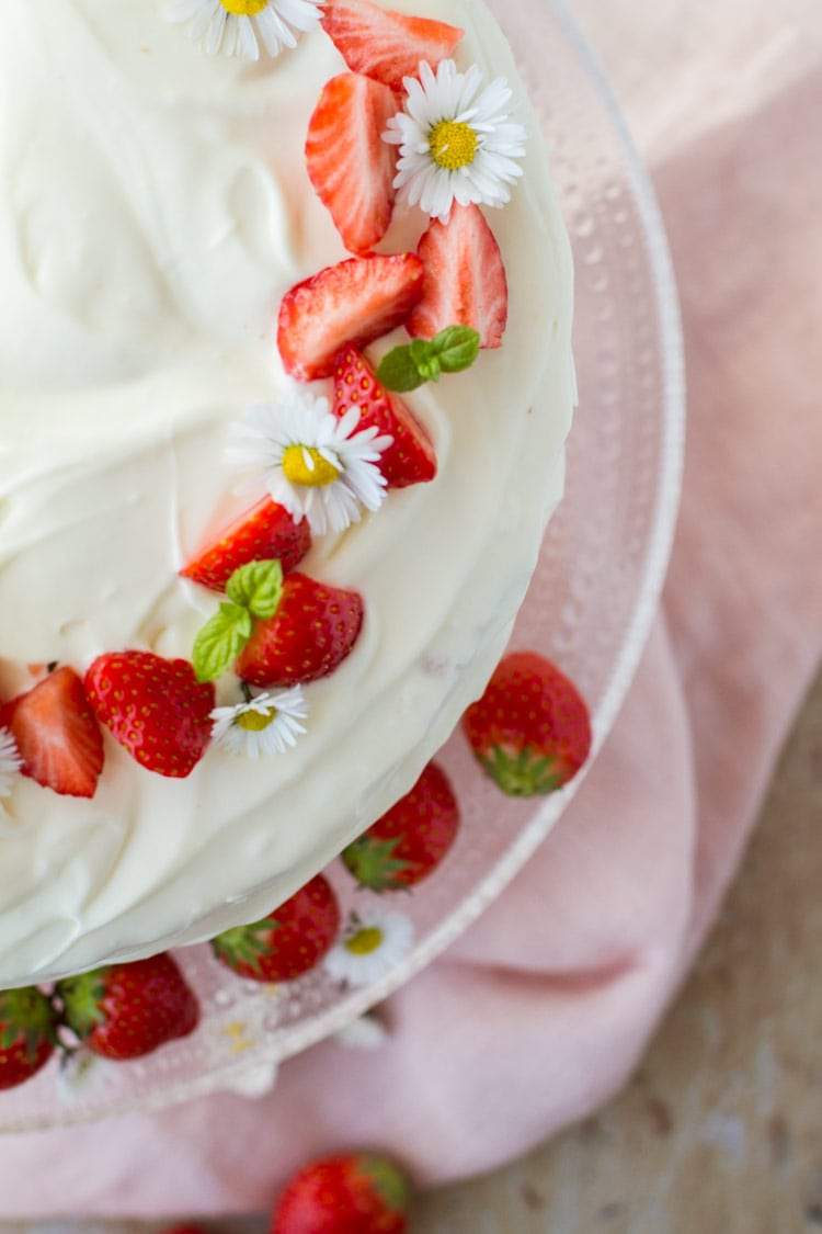 Strawberry cake with sliced strawberries and white flowers as garnish. Close-up, flatlay.